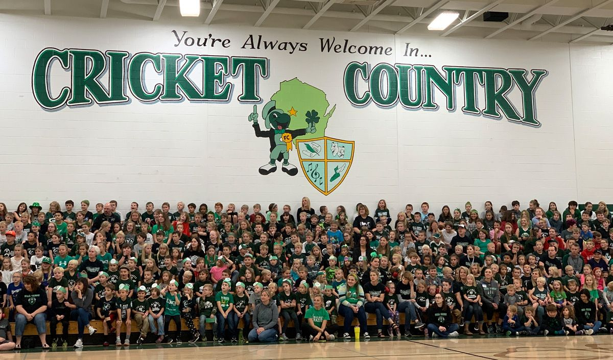 Hundreds of students sit in a gymnasium under the Fall Creek Crickets logo.