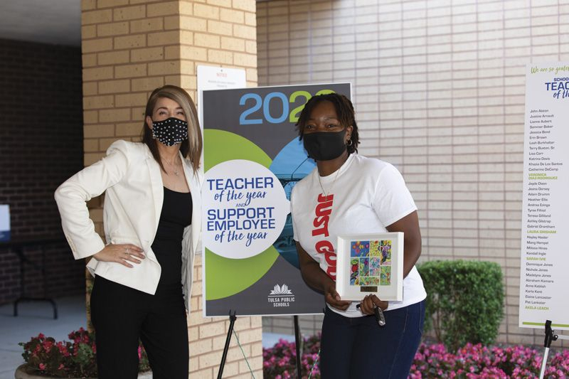 Dr. Gist with a school staff member in front of a Teacher of the Year and Support Employee of the Year poster.