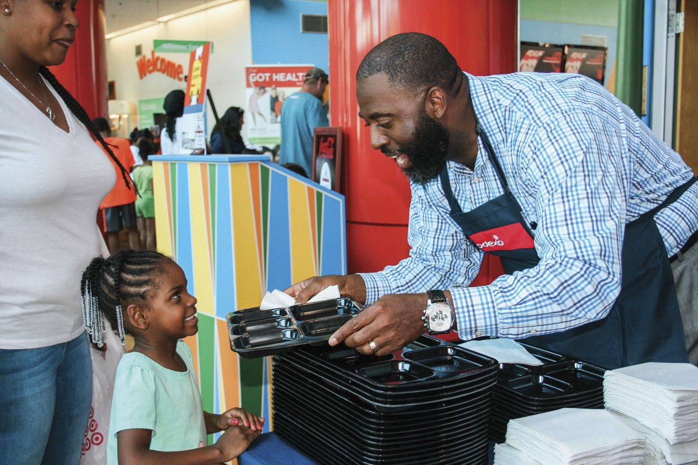 Image: Dr. Barron Davis handing a lunch tray to a smiling young student.