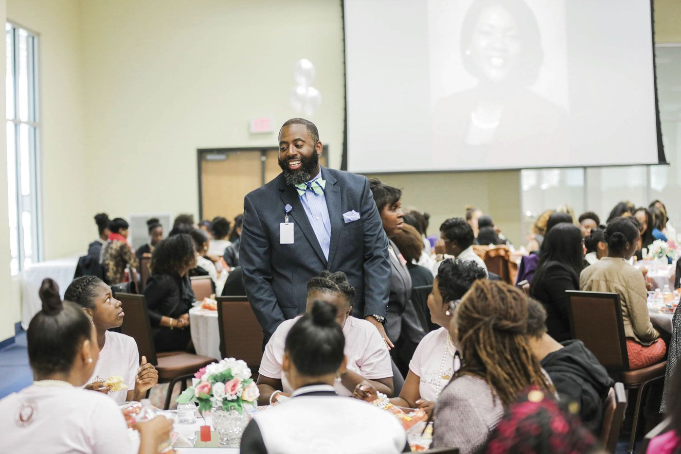 Dr. Barron Davis greets a table of young people during a luncheon.