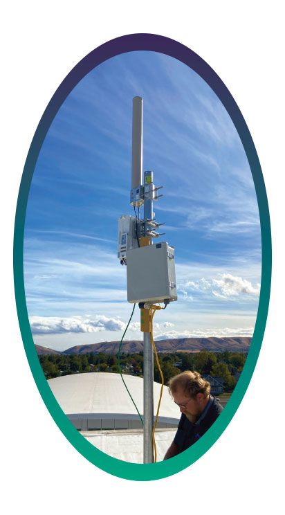 A technician works on one of Yakima School District's WiFi signal boosters.